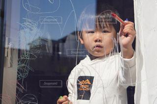 窓にクレヨンで落書きする子供の写真・画像素材[4263306]