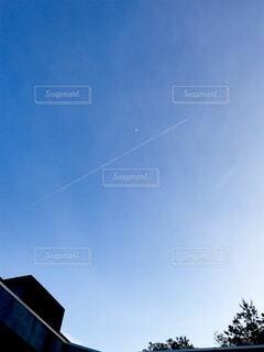 飛行機雲と月の空の写真・画像素材[4160647]