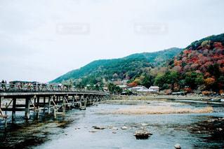 背景の山が付いている水の体の上の橋の写真・画像素材[1002914]