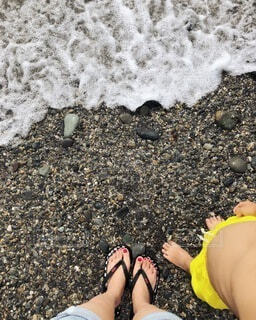 波打ち際で波を待つ母子の写真・画像素材[4171480]