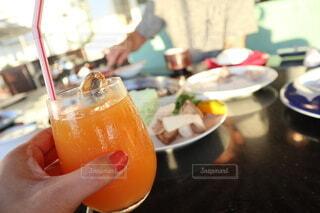 オレンジジュースのグラスを持つ手の写真・画像素材[4178746]