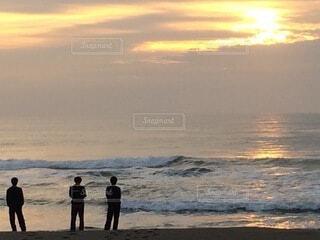 朝焼けの海岸に佇むグループの写真・画像素材[4177175]