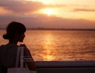 夕暮れの海を見る女性の後ろ姿の写真・画像素材[4213487]