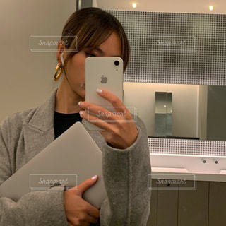 鏡の前に立ってカメラのポーズをとる人の写真・画像素材[3152392]