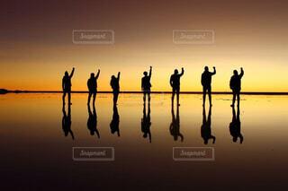 ボリビアのウユニ塩湖で夕暮れの鏡張りを使ってワンピースのポーズの写真・画像素材[4240615]