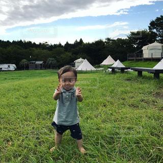 緑豊かな緑のフィールドに立っている少年の写真・画像素材[906316]