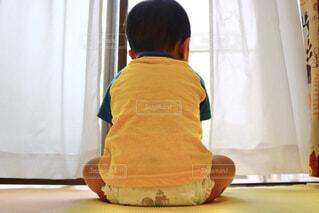 窓の前に後ろ向きに座る子供の写真・画像素材[4243527]