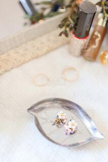 白いハンカチに載っている花の形をしたピアスのアクセサリーの写真・画像素材[4237804]