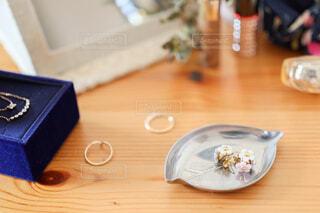 木製のテーブルに載っているお花の形をしたピアスのアクセサリーの写真・画像素材[4237802]