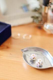木製のテーブルに載っている花の形をしたピアスのアクセサリーの写真・画像素材[4237805]