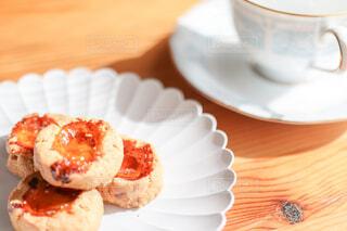 木製のテーブルの白いお皿に載ったクッキーとカップの写真・画像素材[4241973]