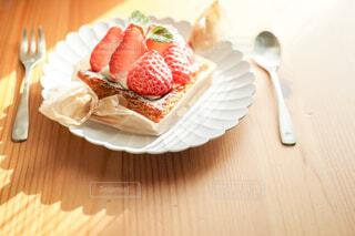 木製のテーブルの白いお皿に載ったイチゴタルトとカトラリーの写真・画像素材[4241993]