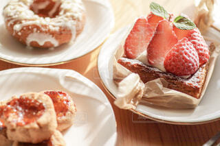ドーナツとクッキーを並べた机の上にあるイチゴタルトのクローズアップの写真・画像素材[4241990]