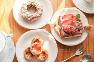 ドーナツとクッキーとケーキとカップかとカトラリーを並べた机の写真・画像素材[4241992]