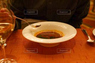 ワイングラスを持ってテーブルに座っている人の写真・画像素材[4272139]