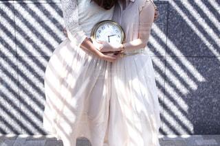 時計の横に立っている人の写真・画像素材[1845814]