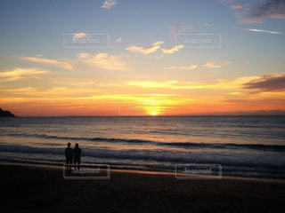 ビーチで夕日を眺めるカップルの写真・画像素材[916792]