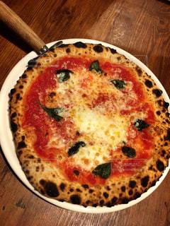 木製のテーブルの上に座ってピザの写真・画像素材[751331]