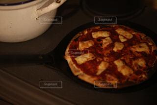 テーブルの上の鍋の上に座っているピザの写真・画像素材[4501105]