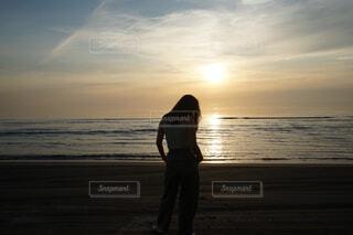夕日を背景にビーチに立ってる人の写真・画像素材[4376598]