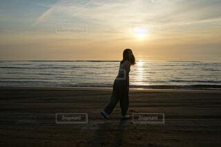 夕日を背景に写真を撮る女性の写真・画像素材[4376599]