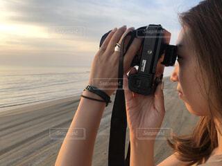 ビーチで夕日の写真を撮る人の写真・画像素材[4379097]