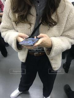 電車の中でスマホを持っている女性の写真・画像素材[4379139]