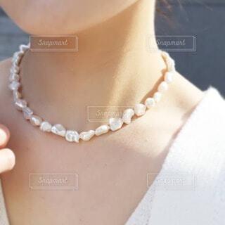 淡水パールのネックレスを付けた女性の首元の写真・画像素材[4372180]