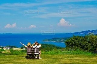 夏の海と空が見えるベンチに座ってばんざいの写真・画像素材[4667647]