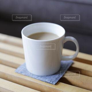 コーヒーテーブルの上にある飲み物が入ったマグカップの写真・画像素材[4405511]