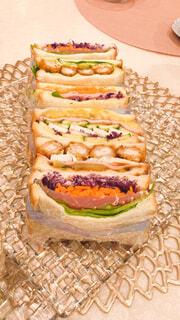 ケーキを入れたまな板の上に座っているサンドイッチの写真・画像素材[4596873]