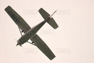 曇り空を飛んでいく軽飛行機の写真・画像素材[4533028]