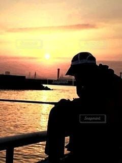 朝日が昇る海づり公園で釣りをしている男性の写真・画像素材[4580800]