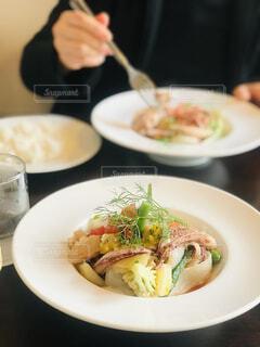 食べ物の皿を持ってテーブルに座っている女性の写真・画像素材[4434840]