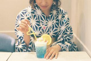コーヒーを飲みながらテーブルに座っている女性の写真・画像素材[4434847]