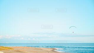 海の隣のビーチで凧を飛ばす人々のグループの写真・画像素材[4465865]