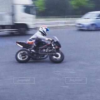 通りをバイクに乗る人の写真・画像素材[4471057]