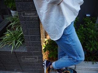 レンガの壁に立ってる人の写真・画像素材[4470572]
