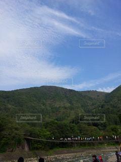 フィールドの背景の山と人々 のグループの写真・画像素材[1104135]