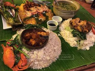 テーブルの上に食べ物のプレートの写真・画像素材[1173192]