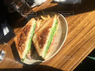 木製のテーブルの上に座って半分サンドイッチのカットの写真・画像素材[1699500]