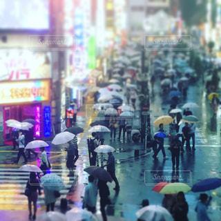 雨の日に通りを歩く人々 のグループの写真・画像素材[878124]