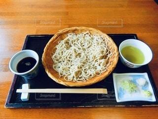 木製のテーブルの上に座っている食べ物のボウルの写真・画像素材[4657671]