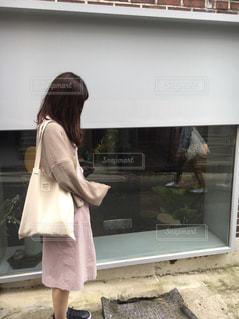 ウィンドウの前に立っている女性の写真・画像素材[855555]