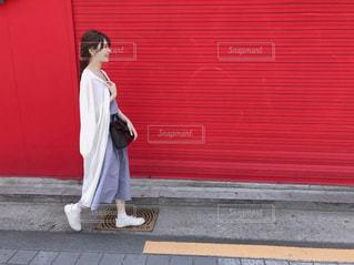 赤い建物の前に立っている人の写真・画像素材[1252087]