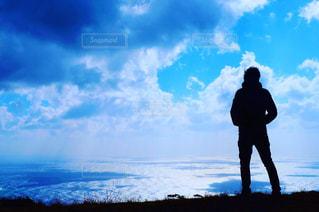 曇り空の前に立っている男の写真・画像素材[969259]