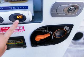 自動販売機で120円の飲み物のボタンを押す人物の手の写真・画像素材[4617268]