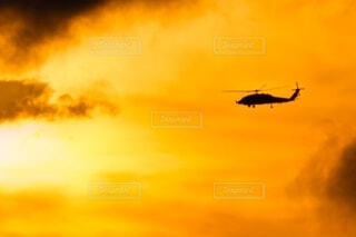 夕焼けを背景に飛ぶヘリコプターの写真・画像素材[4709858]