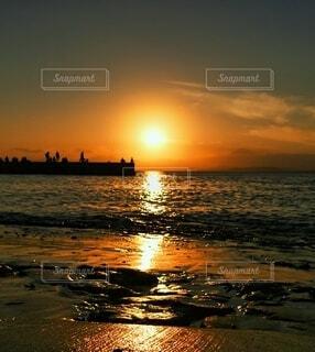 夕焼けと防波堤の人々の写真・画像素材[4930446]