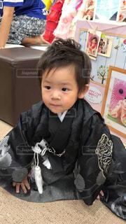 テーブルの上に座っている小さな男の子の写真・画像素材[4591788]
